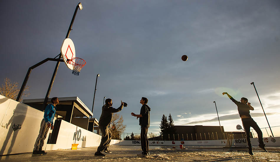 Piyush Laroiya (left), Jagshir Lammay, Harsh Sharma, and Sandeep Phull play basketball on the half-melted ice rink in Whitehorn in Calgary on Friday, Feb. 13, 2015.  The unusually warm day was 12 degrees above zero, and the boys persevered despite the freezing water and slush on the court. (Photo by Mikaela MacKenzie/SAIT Polytechnic)
