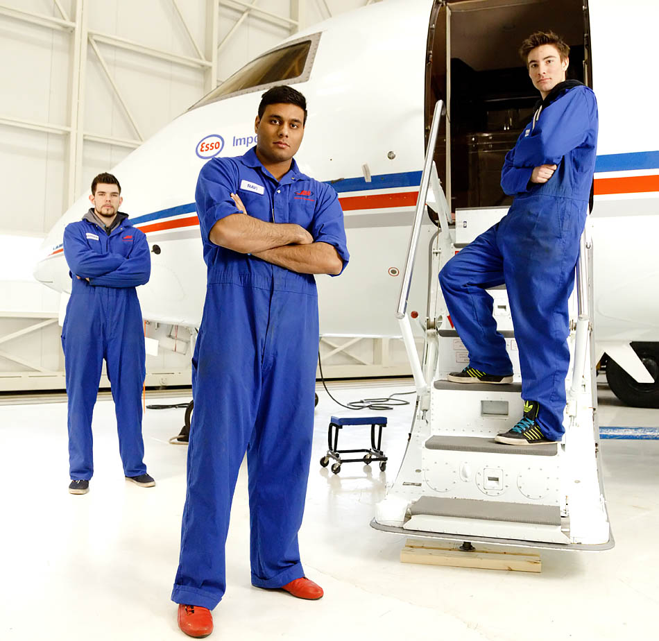 Second-year aircraft maintenance engineer technology student Ravi Bachhal, centre, poses with Morgan Buchner, right, and Braedon Anderson in front of Bombardier Challenger 600 at the Art Smith Aero Centre in Calgary on Wednesday, Feb. 11, 2015. The aircraft maintenance students work on a variety of different aircraft, including large passenger jets and helicopters. (Photo by Aryn Toombs/The Press)