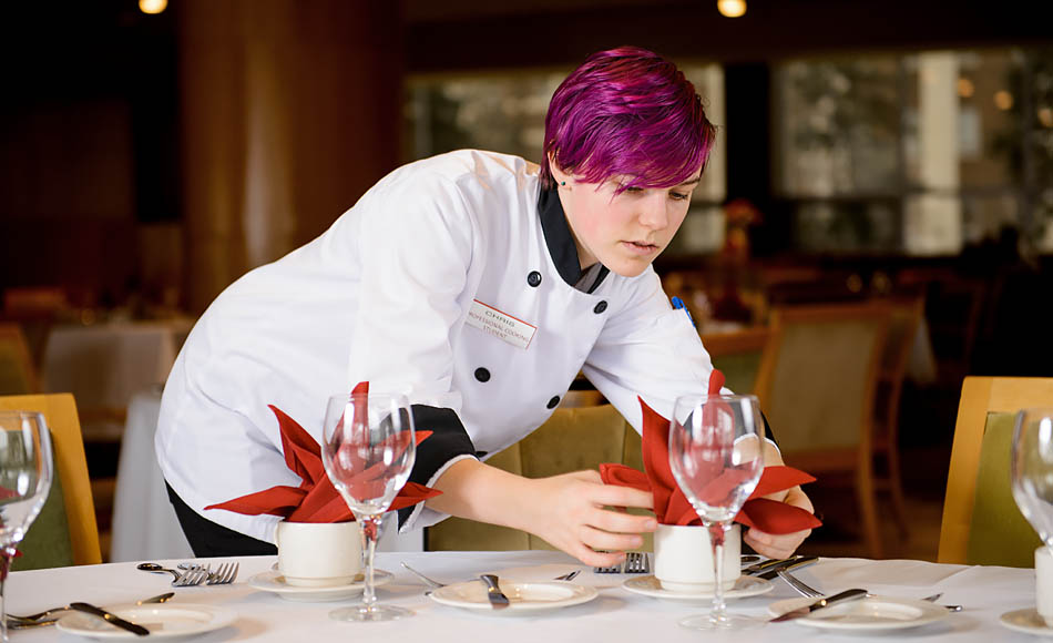 Professional cooking student Chris Armstrong places a napkin on its place on a table in preparation for guests to arrive at the Highwood Dining Room in Calgary on Wednesday, Feb. 11, 2015. Even though Armstrong is enrolled in the professional cooking program, the food and beverage service class sees students preparing the front of the house for diners. Armstrong decided to enter SAIT's cooking program after she became a teaching assistant for her cooking instructor in high school. She plans to pursue her baking apprenticeship and become a journeyman. She hopes to use the universality of her skill set to travel all over the world, working in a location for a few years before moving on and finding a new place to live. (Photo by Nathan Muszynski/The Press)