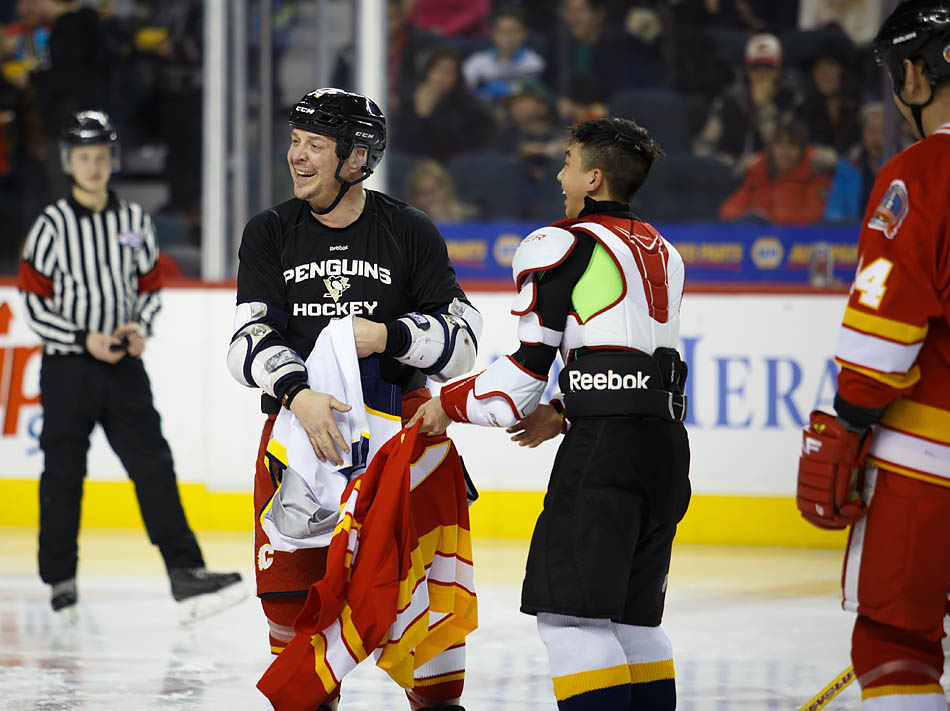 Calgary Flames Alumni play Theo Fleury, left, swaps jerseys with Nathan's Heroes player Jeremy Luu before the second period during the Nathan O'Brien charity hockey game at the Scotiabank Saddledome in Calgary on Thursday, Feb. 5, 2015. The game was put on in support of the Nathan O'Brien Children's Foundation and featured a game between the Calgary Flames Alumni and Nathan's Heroes, a team made up of MLA's, members of the Calgary Police Services and various other local celebrities. (Photo by Zachary Cormier/The Press)