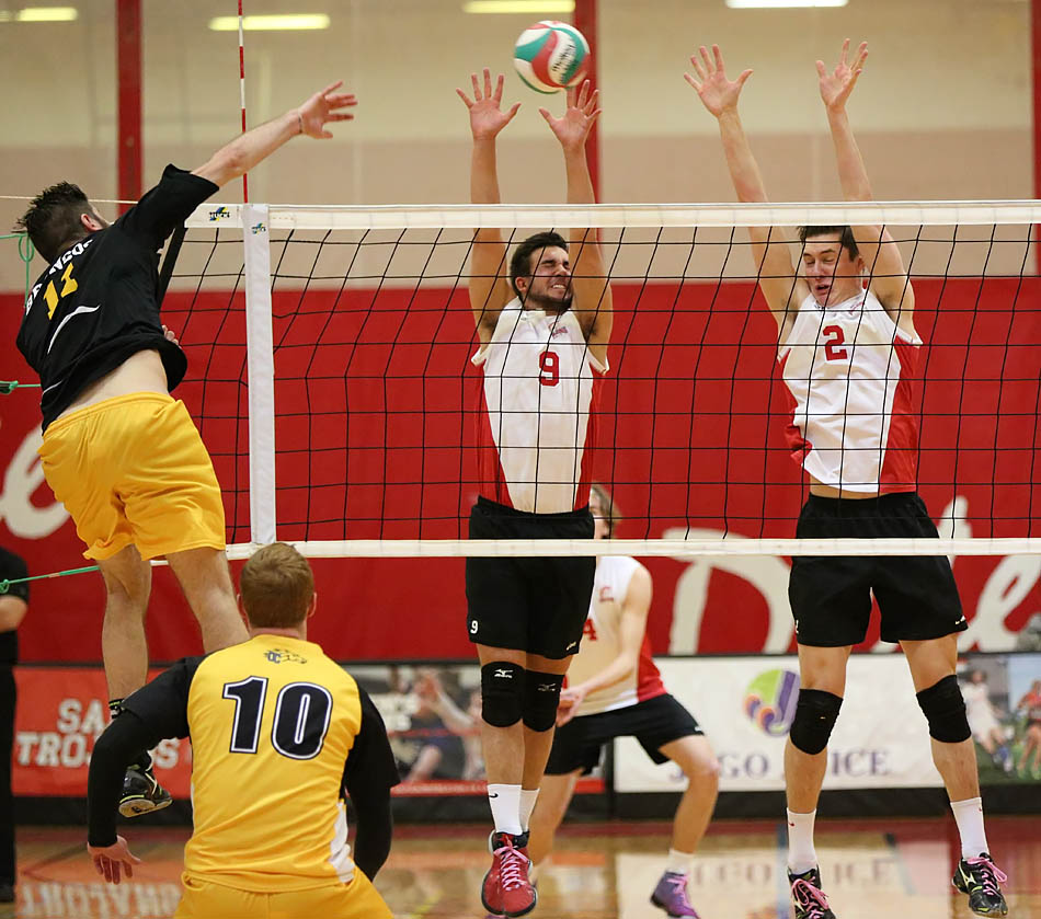Zack Deacon, left, spikes the ball  past Nathan Goss and Brett Bolin at SAIT in Calgary on Sunday, Jan. 25, 2015. close out the win with a 25-12 victory in Set 3. (Photo by Liam Alexander Glass/The Press)