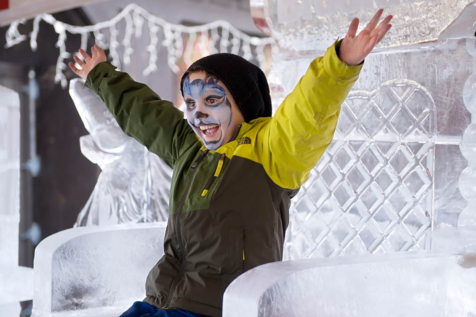 Soney Arthurs raises his arms in victory, having just climbed to the top of a ice carving in the shape of a throne during the Symons Valley Rance Ice Festival in Calgary on Sunday, Jan. 18, 2015. The festivities included an ice carving contest, skating rink, playground, and bonfire. (Photo by Carys Richards/The Press)