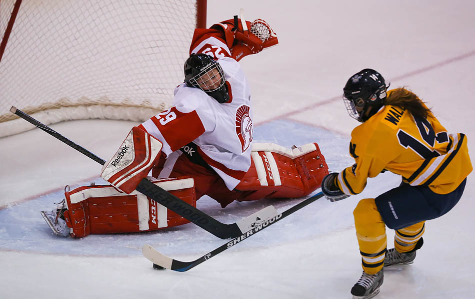 Cheyenne Eagle, left, of the SAIT Trojans lunges across the crease to make a save against Becky Wall of the NAIT Ooks during regular season action at the Campus Centre arena on SAIT Campus in Calgary on Saturday, Nov. 15, 2014. The Trojans fell to the Ooks by a score of 2-0. (Photo by Zachary Cormier/The Press)