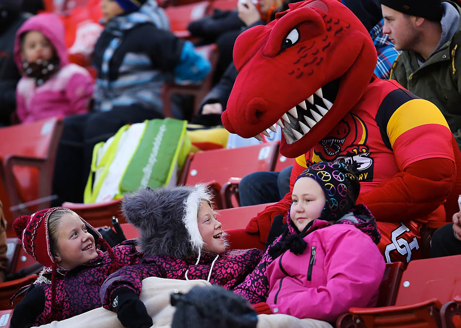 U of C Dinos mascot Rex makes friends with three young Dinos fans during the Hardy Cup final with against the Manitoba Bisons at McMahon Stadium in Calgary on Saturday, Nov. 15, 2014. The Bisons prevailed by a score of 27-15. (Photo by Zachary Cormier/The Press)
