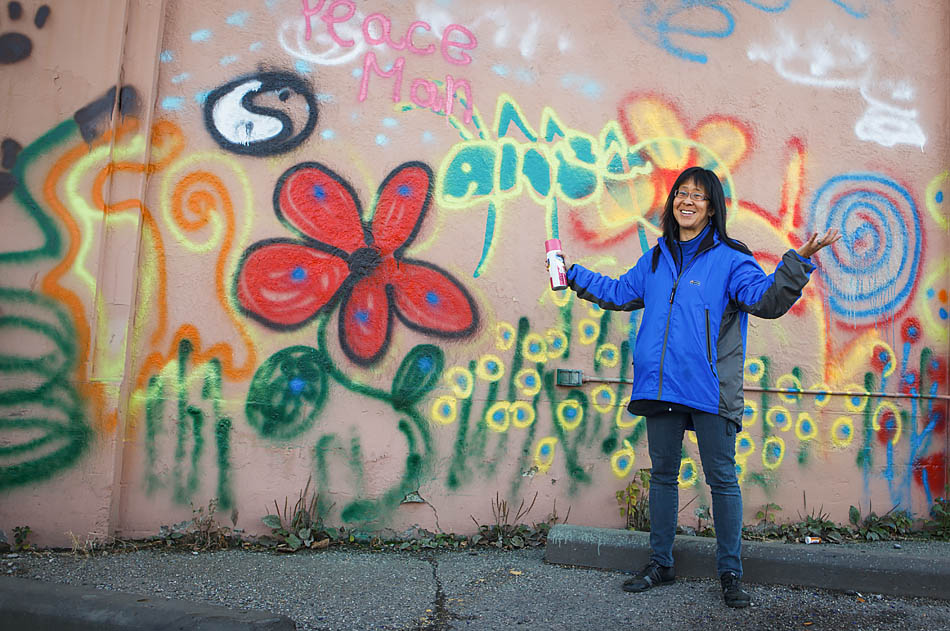 "Tamara Lee, a long-time resident of Kensington, poses in front of the mural she painted on the wall of the historic Ant Hill building in Calgary on Oct. 16, 2014, during an event hosted by Battistella Developments where community members were invited to paint a mural on the building before its demolition. ""I can't believe they are letting us do this, it is so cool,"" exclaimed Lee after completing her portion of the mural. (Photo by Amanda Siebert/The Press)"