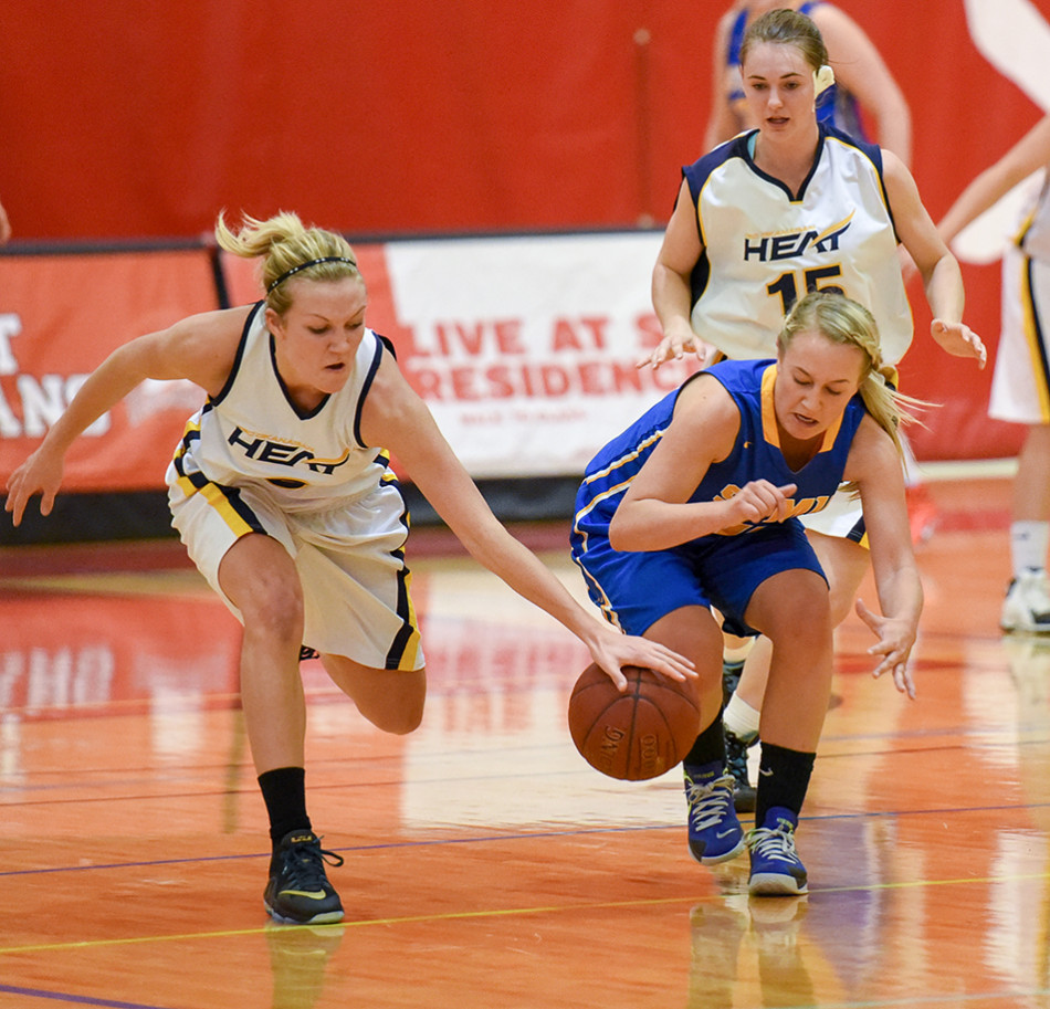 Basketball Battle: UBC Okanagan Heat wing Haylie Gibb strips the ball from Saint Mary's University Lightning guard Laura Belisle during an exhibition game at the SAIT Campus Centre gym. The Heat defeated the Lightening 84-34. (Photo by Kenneth Appleby/The Press)