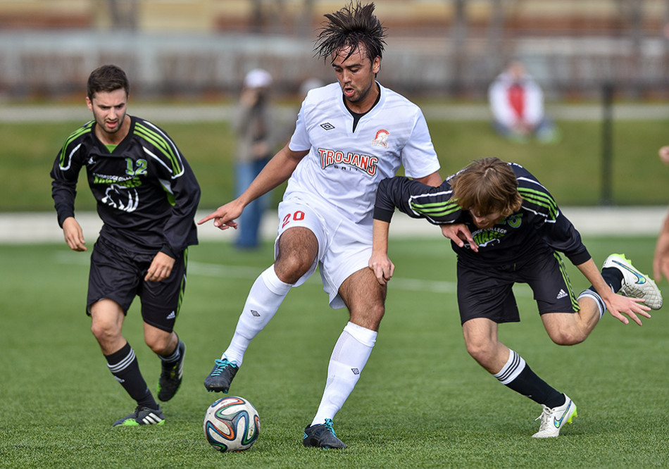 Battle for Control: Lethbridge Kodiaks defence Andrew Southern, left, and midfield Evan Brown, right try to stop Trojans midfielder Yassin Yusuf during ACAC men's soccer action at Cohos Commons Field on SAIT campus. The Kodiaks defeated the Trojans by a score of 3-2. (Photo by Andy Maxwell Mawji/The Press)