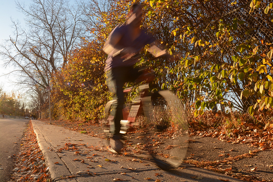 Fall Biking: A biker speeds through a residential area in Calgary. Calgarians have experienced unseasonably mild fall weather this fall. (Photo by Ryan Wellicome/The Press)