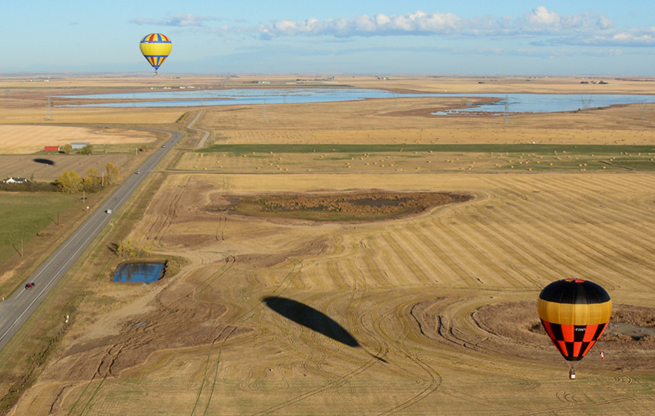 Bird's Eye View: The balloons Salsa, left, and Black Magic compete in the Heritage Inn International Balloon Festival in High River. Black Magic ended up taking first place in the competition. (Photo by Kelsey Yates/The Press)