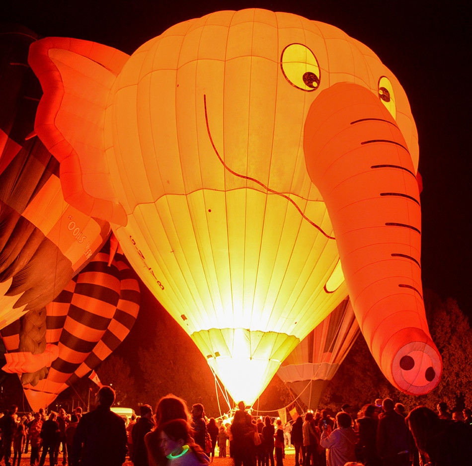 Lighted Balloons: Spectators gaze at the pink elephant balloon, Nelly-B, at the Heritage Inn International Balloon Festival in High River. Each night of the balloon festival, the pilots ignite the propane burners to light up the balloons for all to enjoy. (Photo by Kelsey Yates/The Press)