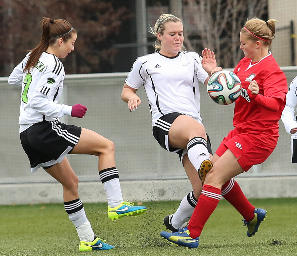 My Ball: Red Deer Queen midfielder Angela Vanderburg, centre, scuffles with Trojans centre back Roshell Organ during ACAC women's soccer action at Cohos Commons Field on SAIT campus.(Photo by Liam Quinn/The Press)