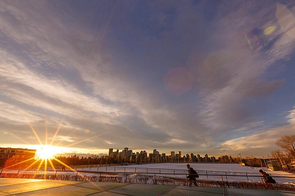 Starburst: People navigate SAIT campus as the sun rises over downtown Calgary on Thursday, Feb. 16, 2017. The day was uncharacteristically warm for mid-February in Calgary, with temperatures reaching a high of 14 degrees Celsius. (Photo by Nikolai Cuthill/The Press)