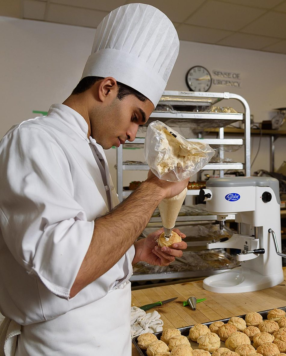 Primp and Proper Professional cooking student, Armaan Kukkadi, fills profiteroles with a pastry cream in the John Ware building on SAIT's main campus in Calgary on Thursday, Feb. 16, 2017. A profiterole is a filled French choux pastry ball with a typically sweet and moist filling of whipped cream, custard, pastry cream, or ice cream. Savory profiteroles can also be made and filled with pureed meats, cheese as well as being garnished for soup when desired. (Photo by Pier Moreno Silvestri/The Press)