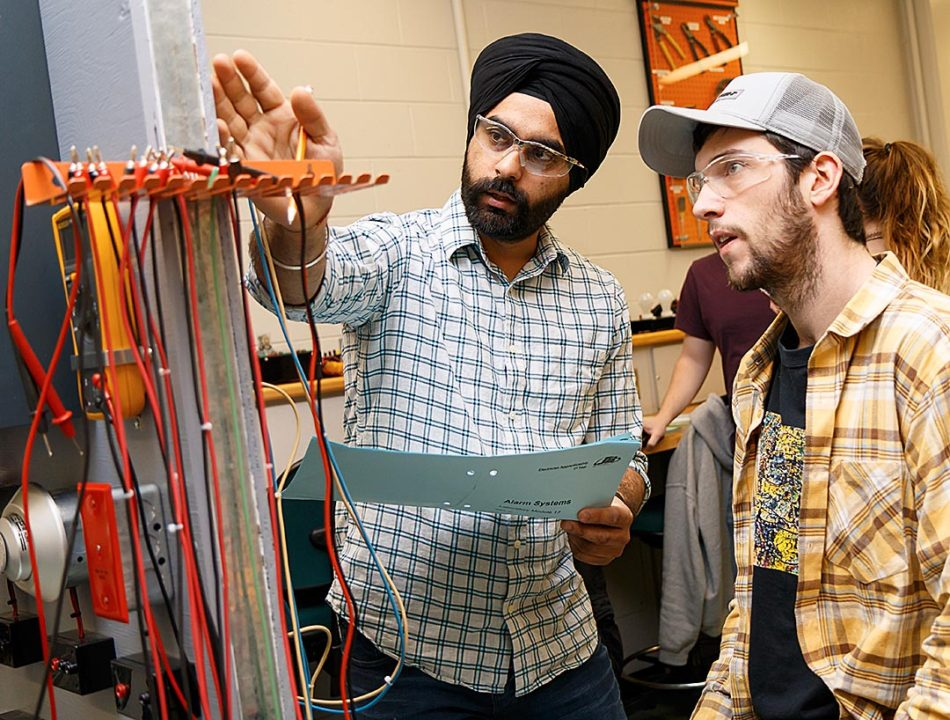 All Secured: Maninderjeet Singh, left, and Thomas Coker work with a mock setup in an alarm systems lab as part of the electrical engineering program in Calgary on Thursday, Feb. 16, 2017. In the lab, students learned how to install, repair and read alarm systems typically found in North American homes. (Photo by Parker Crook/The Press)
