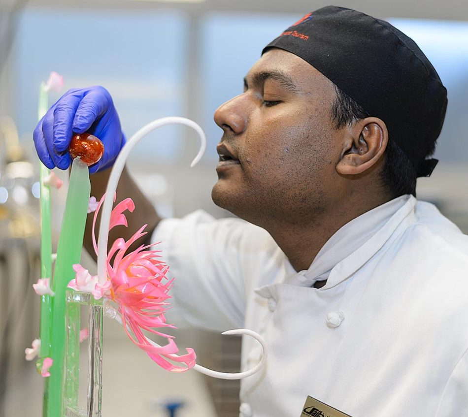 The Cherry on Top: Waleed Sabur, a second-year baking and pastry arts student, cools off a cherry made of sugar during class in the basement of the John Ware Building in Calgary on Thursday, Feb. 16, 2017. Sabur, originally from Bangladesh, came to Canada to work but drove past SAIT one day and decided to pursue a career in his passion for baking. (Photo by Ashley Orzel/The Press)